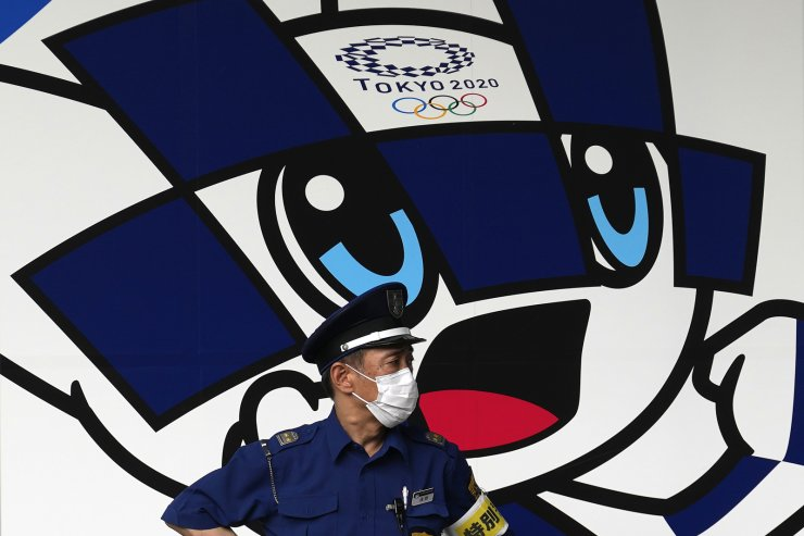 A security guard wearing a mask to help protect against the spread of the coronavirus stands at a wall with Tokyo 2020 Olympics mascot Miraitowa Tuesday, July 13, 2021, in Tokyo. The Olympics begin July 23. AP