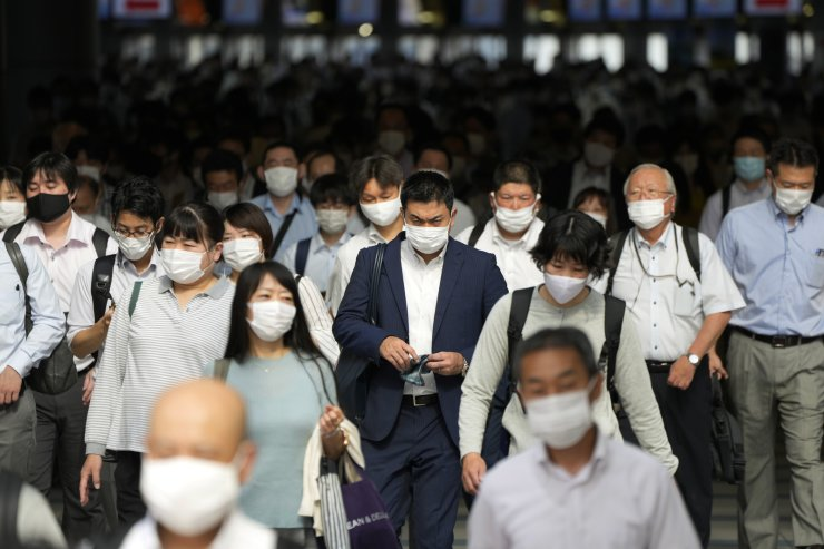 Commuters wearing face masks walk in a passageway during a rush hour at Shinagawa Station Monday, July 12, 2021, in Tokyo. Japan declared the fourth state of emergency for Tokyo from Monday until Aug. 22. AP