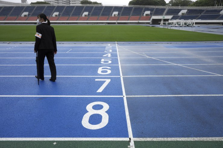 A police officer stands at empty race track after the unveiling ceremony for Olympic Flame of the Tokyo 2020 Olympic torch relay at Komazawa Olympic Park, which was initially built for the 1964 Tokyo Olympic Games, Friday, July 9, 2021, in Tokyo. AP
