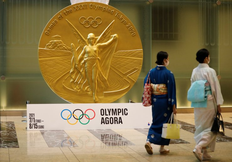 Women wearing protective masks, following the coronavirus disease (COVID-19) outbreak, walk past a large-scale reproduction of Tokyo 2020 Olympic Games medal at Nihonbashi Mitsui Tower in Tokyo, Japan, July 14. REUTERS