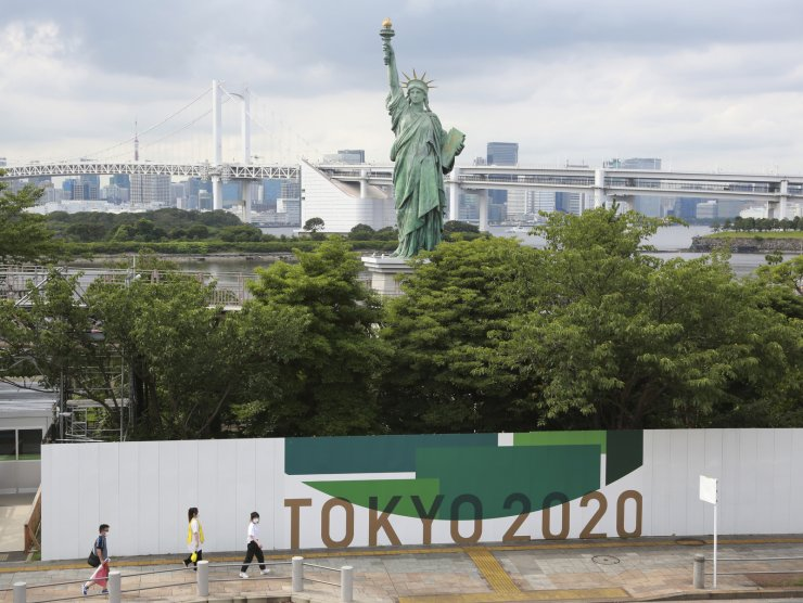 People walk by posters to promote Tokyo 2020 Olympics in Tokyo, Wednesday, July 14, 2021. The Olympic Games are scheduled to begin on July 23. AP