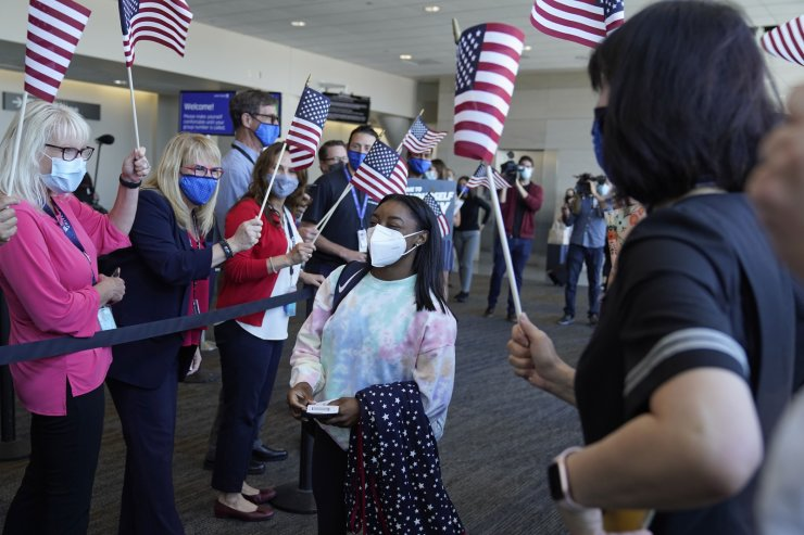 Simone Biles walks to her gate for her flight to the Summer Olympic Games in Tokyo as United Airlines employees wave flags during a send-off event for the U.S. Women's Gymnastics team at the San Francisco International Airport on Wednesday, July 14. AP