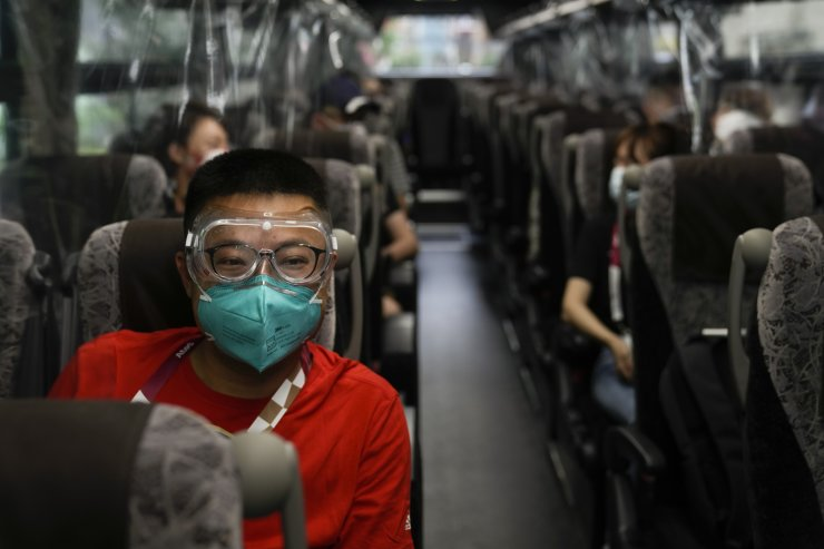 Hua Zhang, of the China Media Group, wears protective goggles while riding a media bus ahead the 2020 Summer Olympics, Wednesday, July 14, 2021, in Tokyo. The state of emergency will be in effect throughout the entire duration of the Olympics, which open on July 23. AP