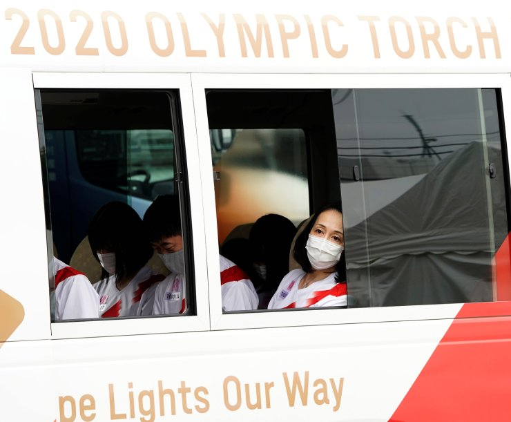 Torchbearers sit in a vehicle as they wait for the start of a lighting ceremony during which they pass the flame to the next torchbearers via a torch kiss, after their relay on a public road was cancelled due to the coronavirus disease (COVID-19) pandemic, at the Tokyo 2020 Olympic torch relay celebration in Tokyo, Japan, July 9. REUTERS