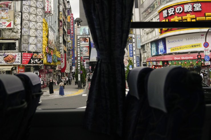Kabukicho, Tokyo's entertainment district, is seen from a bus ahead of the 2020 Summer Olympics, Wednesday, July 14, 2021, in Tokyo. The state of emergency will be in effect throughout the entire duration of the Olympics, which open on July 23. AP
