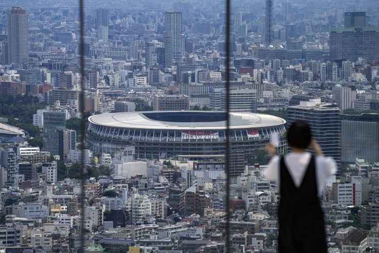 A person wearing a protective mask takes a picture from an observation deck as National Stadium, where the opening ceremony of the Tokyo 2020 Olympics will be held in less than two weeks is seen in the background Saturday, July 10, 2021, in Tokyo. AP
