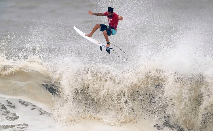 Brazil's Italo Ferreira goes to the air during the quarterfinals of the men's surfing competition at the 2020 Summer Olympics, Tuesday, July 27, 2021, at Tsurigasaki beach in Ichinomiya, Japan. AP