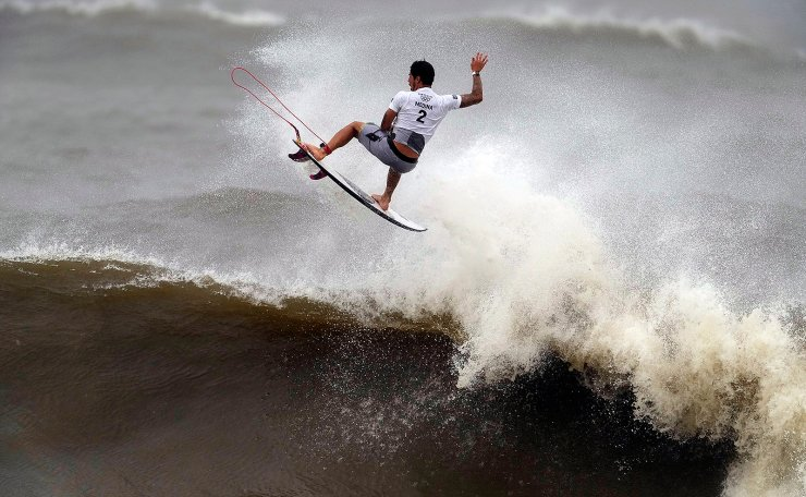 Brazil's Gabriel Medina goes to the air during the quarterfinals of the men's surfing competition at the 2020 Summer Olympics, Tuesday, July 27, 2021, at Tsurigasaki beach in Ichinomiya, Japan. AP