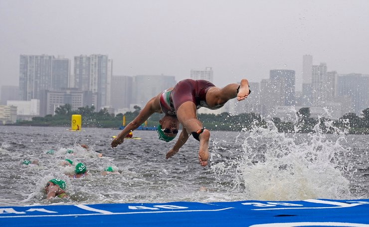 Zsofia Kovacs of Hungary dives into the water for her second lap during the swim leg of the women's individual triathlon competition at the 2020 Summer Olympics, Tuesday, July 27, 2021, in Tokyo, Japan. AP