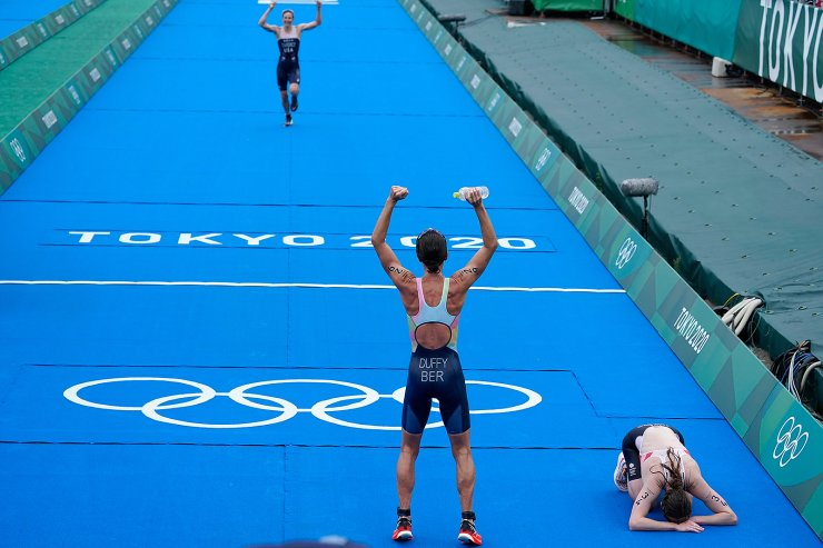 Gold medal winner Flora Duffy of Bermuda cheers on bronze medalist Katie Zaferes of The United States as she approaches the finish, while silver medalist Georgia Taylor-Brown of Great Britain collapses on the ground after finishing during the women's individual triathlon competition at the 2020 Summer Olympics, Tuesday, July 27, 2021, in Tokyo, Japan. AP