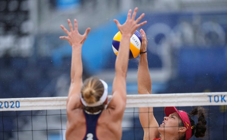 Elsa Baquerizo McMillan, of Spain, right, of Spain, takes a shot as Alix Klimeman, of the United States, defends during a women's beach volleyball match at the 2020 Summer Olympics, Tuesday, July 27, 2021, in Tokyo, Japan. AP
