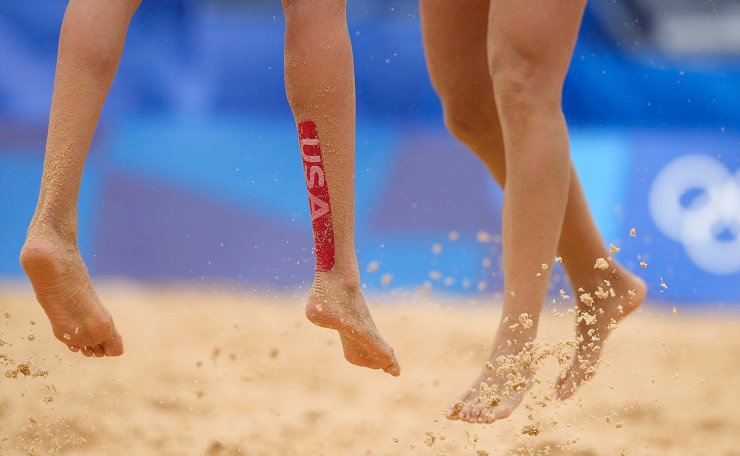 Alix Klimeman, left, of the United States, wears a USA tape during a women's beach volleyball match against Spain at the 2020 Summer Olympics, Tuesday, July 27, 2021, in Tokyo, Japan. AP