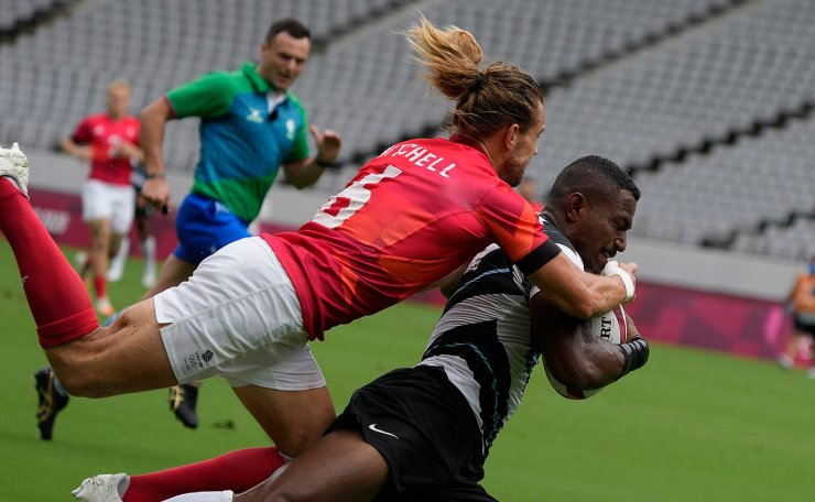 Fiji's Jiuta Wainiqolo is tackled by Britain's Tom Mitchell as he comes in to score a try, in their men's rugby sevens match at the 2020 Summer Olympics, Tuesday, July 27, 2021 in Tokyo, Japan. AP