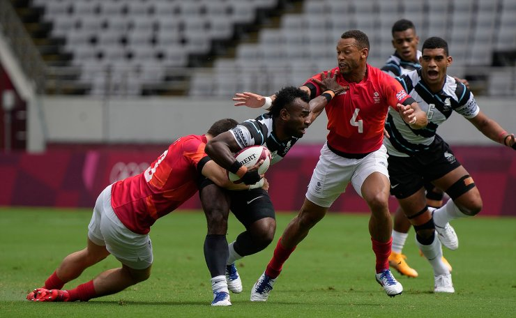 Fiji's Jerry Tuwai is tackled by Canada's Mike Fuailefau as he holds back Canada's Phil Berna, in their men's rugby sevens match at the 2020 Summer Olympics, Tuesday, July 27, 2021 in Tokyo, Japan. AP
