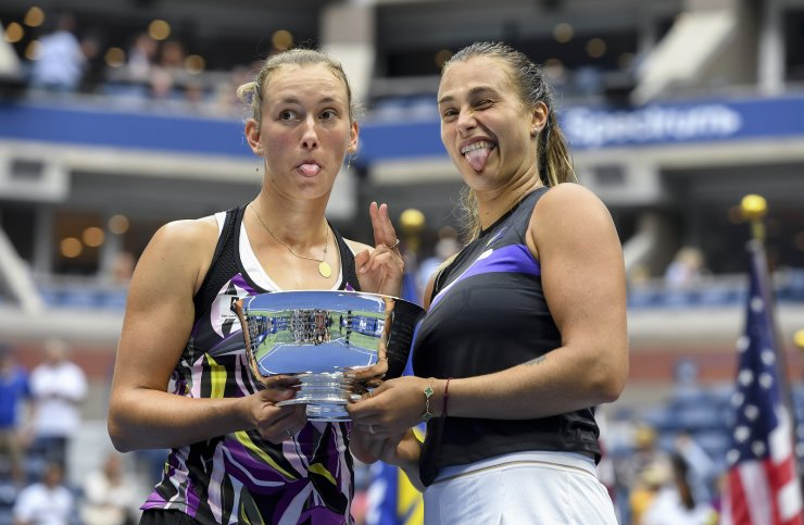 Elise Mertens, of Belgium, left, poses for photos with the trophy with doubles partner Arena Sabalenka, of Belarus, after winning the women's doubles final against Victoria Azarenka, of Belarus, and Ashleigh Barty, of Australia, at the U.S. Open tennis championships Sunday, Sept. 8, 2019, in New York. AP