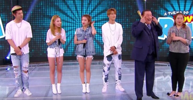 Raul Gil, host of 'Turma Do Vovo Raul' on SBT, makes slit eyes at the audience with K-pop band KARD and an interpreter behind him. / Screen capture from YouTube