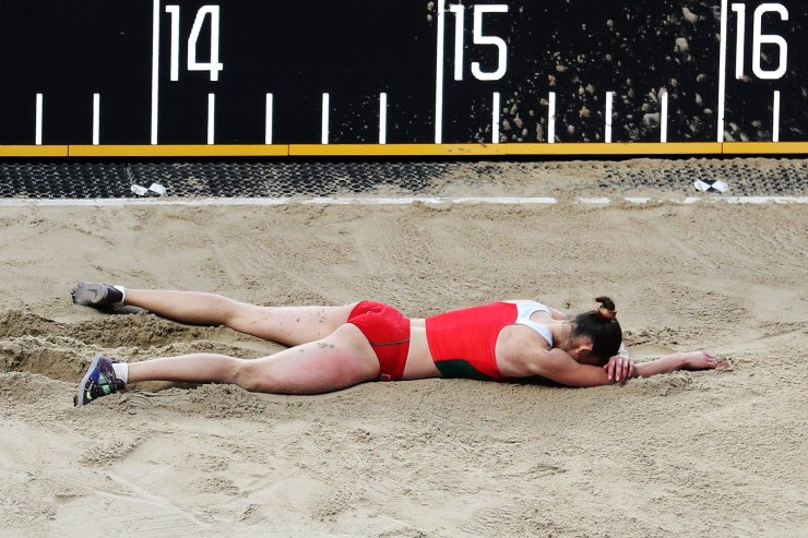 Iryna Vaskouskaya of Belarus lies on the sand during the women's triple jump qualification at the 2019 IAAF World Athletics Championships in Doha, Qatar, Oct. 3, 2019. Xinhua