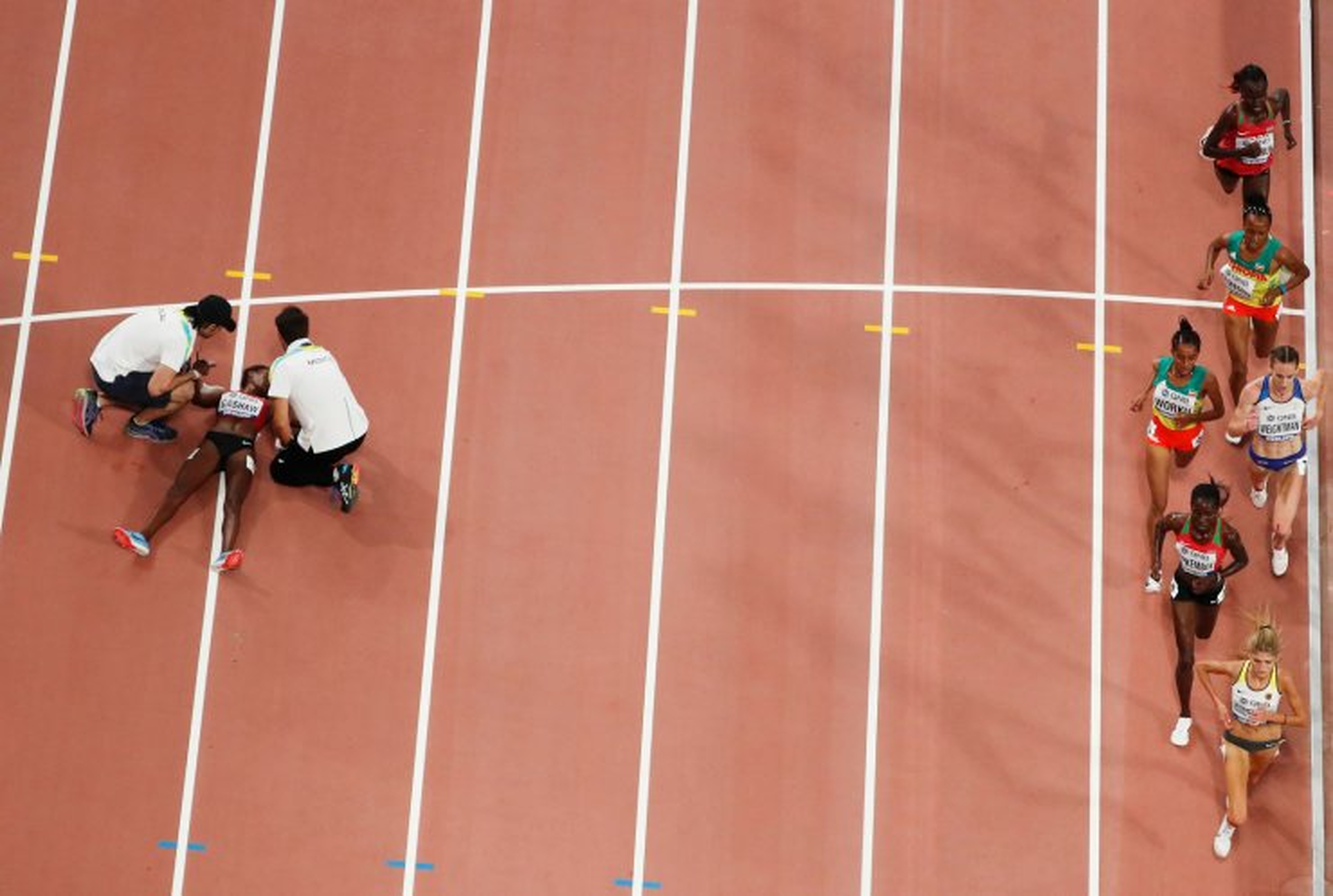 Athletics - World Athletics Championships - Doha 2019 - Women's 5000 Metres Heats - Khalifa International Stadium, Doha, Qatar - October 2, 2019  Bahrain's Tigist Gashaw receives medical attention while athletes compete  REUTERS