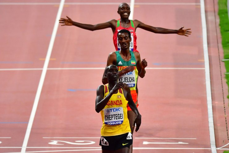 Uganda's Joshua Cheptegei (front) crosses the finish line to win the Men's 10,000m final ahead of Ethiopia's Yomif Kejelcha (C) and Kenya's Rhonex Kipruto at the 2019 IAAF Athletics World Championships at the Khalifa International stadium in Doha on October 6, 2019. AFP