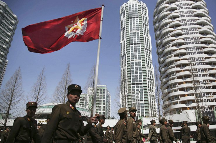 North Korean soldiers carry the Korean People's Army flag as they walk past residential buildings along Ryomyong street in Pyongyang, North Korea, Apr. 13. / AP-Yonhap