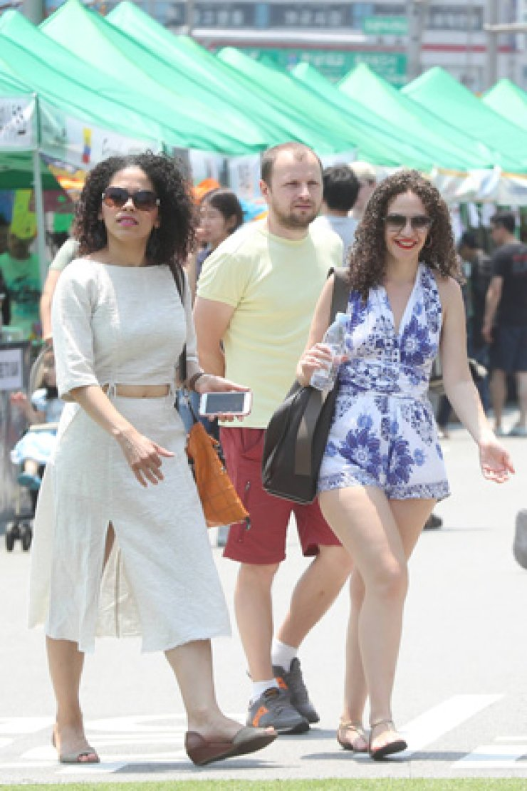 Foreigners stroll around a Latin American cultural event on Jangchungdan-ro in Jung-gu, Seoul, June 18. / Yonhap