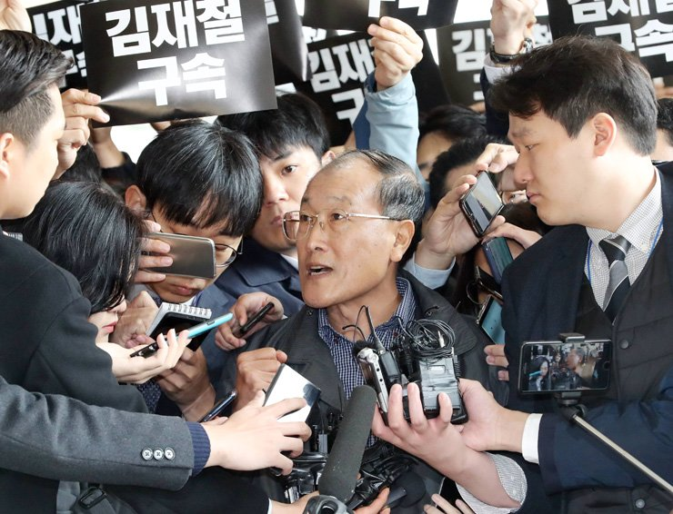 Former chief of television broadcaster MBC Kim Jae-chul, center, answers journalists' questions as he visits the Seoul Central District Prosecutors' Office in Seocho-gu, Seoul, for questioning, Monday, on charges of helping a previous government seize control of the broadcaster. Posters behind Kim read 'Arrest Kim Jae-chul.' / Yonhap