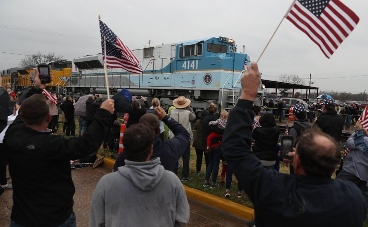 People wave at the train carrying the casket of former U.S. President George H.W. Bush to the George H.W. Bush Presidential Library at Texas A&M University on December 6, 2018 in Navasota, Texas. AFP
