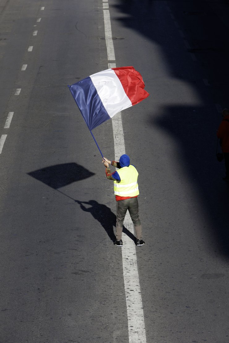 A demonstrator wearing a yellow vest waves the French flag during a march Saturday, Dec. 8, 2018 in Marseille, southern France. AP