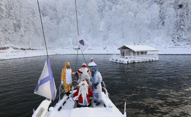 Members of the 'Skipper' yacht club dressed as Santa Claus, its Russian equivalent Ded Moroz, his granddaughter Snegurochka (Snow Maiden) and in a fancy dress of giraffe sail a yacht along the Yenisei river while marking the end of the sailboat season, with the air temperature at about -7 degrees Celsius, outside Siberian city of Krasnoyarsk, Russia December 8, 2018. Reuters