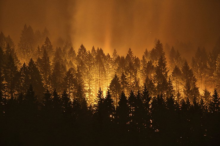 FILE - This Sept. 5, 2017 file photo shows the Eagle Creek wildfire burning on the Oregon side of the Columbia River Gorge near Cascade Locks, Ore. Researchers at the University of Idaho say the amount of carbon dioxide being released into the atmosphere from forest fires in the U.S. West is being greatly overestimated, possibly leading to poor land management decisions. Researchers in the study published last week in the journal Global Change Biology say many estimates are 59% to 83% higher than what is found based on field observations. AP