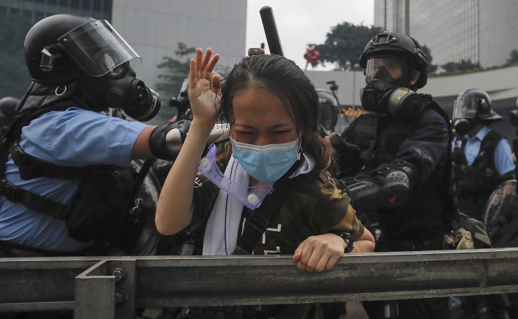 In this Wednesday, June 12, 2019, file photo, a protester reacts as she tackled by riot police during a massive demonstration outside the Legislative Council in Hong Kong. AP