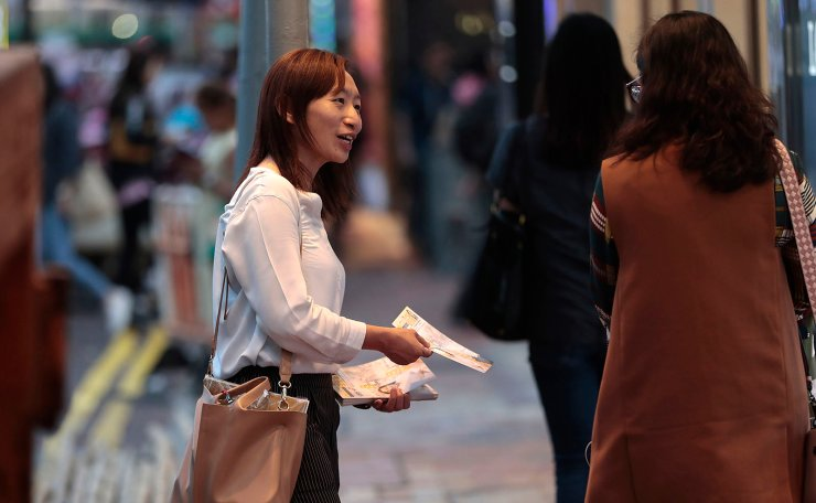 In this photo taken Thursday, Nov. 7, 2019, district council candidate Cathy Yau distributes flyers to pedestrians during her campaign at Causeway Bay in Hong Kong. Yau. a former police officer, grew exasperated as police used more force to quell the unrest. She quit the force in July after 11 years and is running in Sunday's district polls that are widely expected to deliver a decisive victory for the six-month-old movement seeking democratic reforms in the semi-autonomous Chinese territory. AP