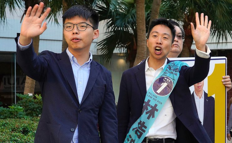 Pro-democracy activist Joshua Wong, left, campaigns with local election candidate Kelvin Lam, right, in Hong Kong, Saturday, Nov. 23, 2019. Chanting 'No more tear gas,' dozens of Hong Kong families with young children are marching to oppose the government's handling of protests on the eve of keenly contested local elections. AP
