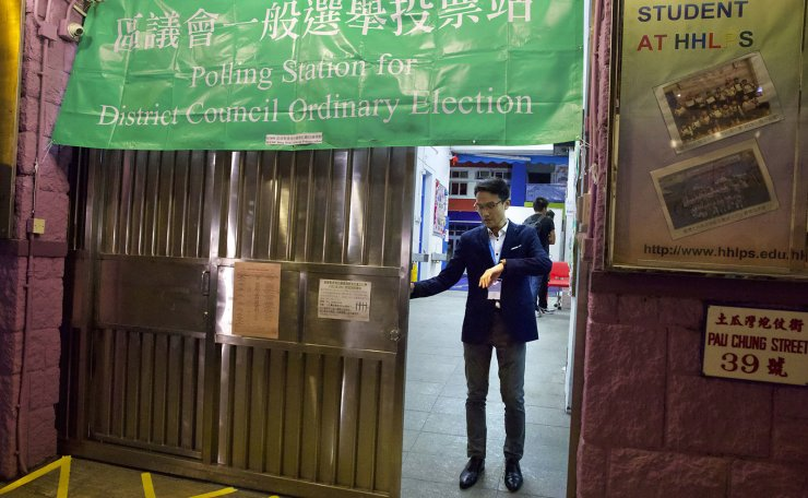An election worker checks his watch before closing the gate on a polling place in Kowloon City in Hong Kong, Sunday, Nov. 24, 2019. AP