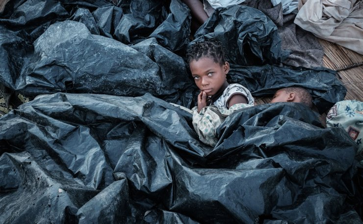 Enia Joaquin Luis, 11, wakes up beside her sister Luisa, 6, under plastic sheets for protect themselves from rain as they stay in shelter at the stands of Ring ground in Buzi, Mozambique, on March 23, 2019. - The death toll in Mozambique on March 23, 2019 climbed to 417 after a cyclone pummelled swathes of the southern African country, flooding thousands of square kilometres, as the UN stepped up calls for more help for survivors. Cyclone Idai smashed into the coast of central Mozambique last week, unleashing hurricane-force winds and rains that flooded the hinterland and drenched eastern Zimbabwe leaving a trail of destruction. AFP