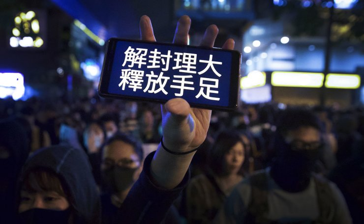 A masked protester flash her smartphone bearing the words 'Unblock Polytechnic University, release our people' as they gather near the University to urge authorities to release the remaining trapped protesters, in Hong Kong, Monday, Nov. 25, 2019. AP