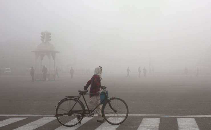 FILE - This Jan. 18, 2019 file photo shows a cyclist amidst morning smog in New Delhi, India. Beth Gardiner's new book 'Choked' documents how air pollution is responsible for seven million premature deaths around the world. AP
