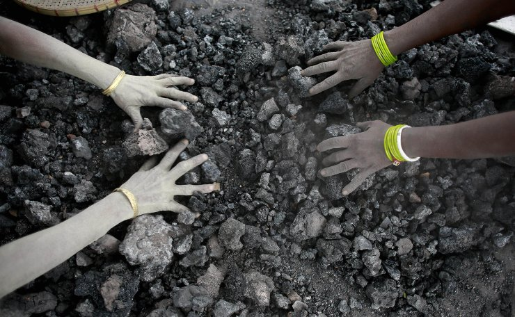 FILE - In this Monday, Dec. 14, 2015, file photo, Indian women use bare hands to pick reusable pieces from heaps of used coal discarded by a carbon factory in Gauhati, India. AP