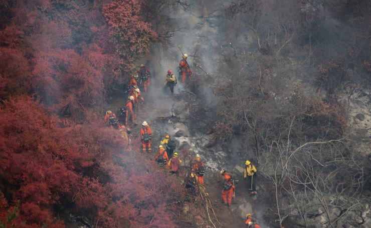 An inmate hand crew, wearing orange, uses chain saws and hand tools to cut a line through vegetation that is reddened by fire retardant on one side and charred by fire on the other at a wildfire dubbed the Cave Fire, burning in the hills of Santa Barbara, California, U.S., November 26, 2019. Reuters
