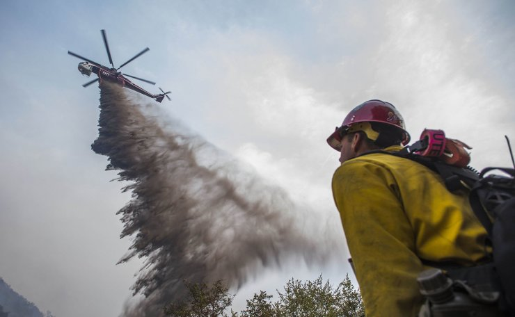A helicopter drops fire retardant over the Cave Fire at Los Padres National Forest on November 26, 2019 in Santa Barbara, California. Officials say the fire is now 10 percent contained. AFP