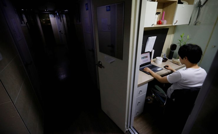 Kim Jae-hoon uses his laptop in his cubicle, called a goshi-won, where he lives in Suwon, South Korea, October 30, 2019. REUTERS/Kim Hong-Ji