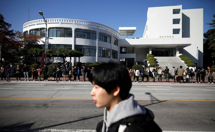 Kim Jae-hoon walks past people waiting at a bus stop, as he makes his way to Kyung Hee University in Suwon, South Korea, October 30, 2019. REUTERS/Kim Hong-Ji