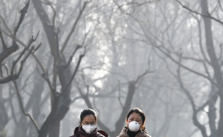 FILE - In this Dec. 19, 2016, file photo, women wearing masks to protect themselves from air pollution walk through Ritan Park shrouded by dense smog in Beijing. China says it has realized its 2020 target for reducing carbon emissions ahead of schedule. The ecology and environment ministry published a report Wednesday saying China's CO2 emissions per unit of GDP had fallen last year by 4% from a year earlier to stand at 45.8% less than in 2005. That completed the reduction target for 2020 ahead of schedule. AP