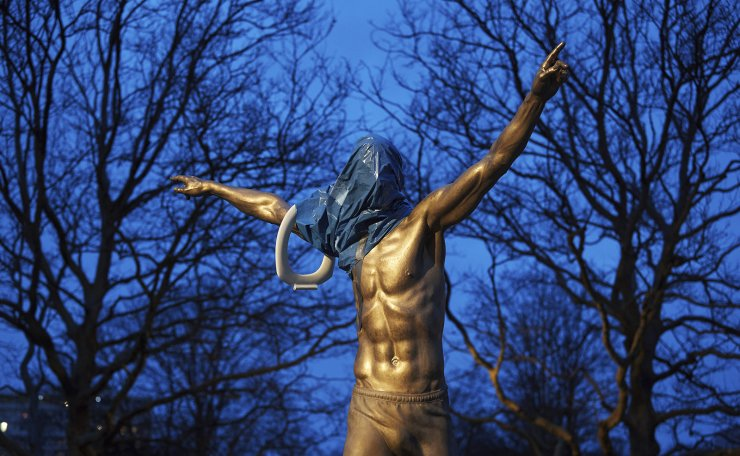 A blue plastic bag and a toilet seat hangs from the statue of the Swedish football player Zlatan Ibrahimovic in Malmo, Wednesday Nov. 27, 2019. A fence has been placed around a statue of Zlatan Ibrahimovic and security guards have been keeping watch after it was vandalized by Malmo soccer fans furious at the Swedish soccer star buying a stake in a rival club. AP
