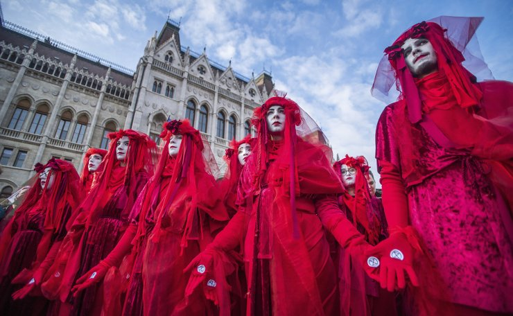 Activists of Extinction Rebellion sport red clothes as they demonstrate with other young environmentalists to demand measures against climate change in front of the Parliament building, rear, in Budapest, Hungary, Friday, Nov. 29, 2019. The protest was held by the movements Fridays For Future Hungary and Extinction Rebellion Hungary. AP