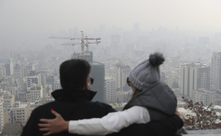 People look at the view of Tehran through polluted air, Iran, in the Velenjak mountainous area, Saturday, Nov. 30, 2019. The air pollution forced authorities to close down all kindergartens, schools and universities on Saturday. AP
