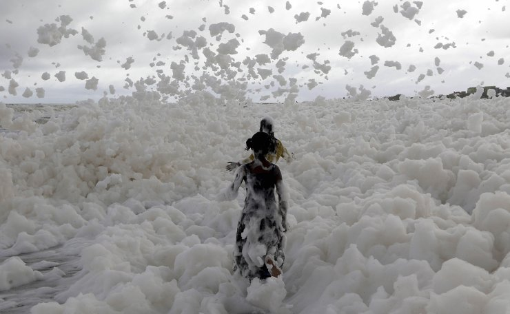Children play on the Marina beach on the Bay of Bengal coast which is blanketed in sea foam in Chennai, India, Sunday, Dec.1, 2019. AP