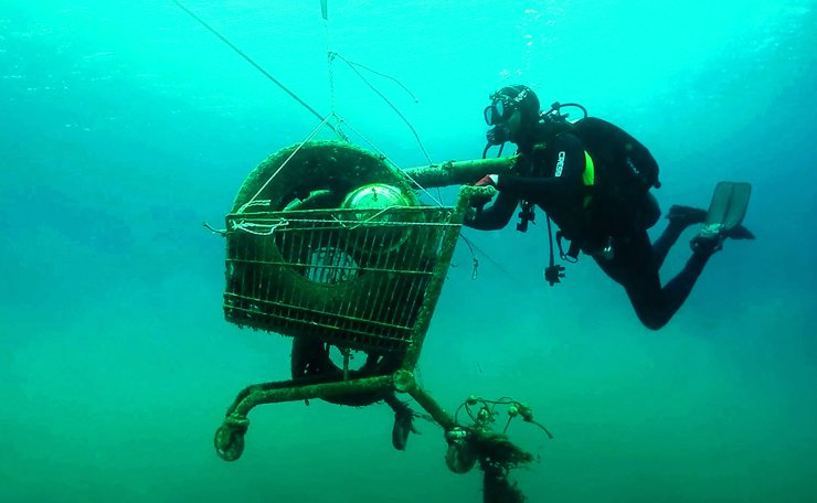 This handout picture taken in 2019 and released on November 30, 2019 by the Aegean Rebreath, a Greek organisation formed in 2017, shows volunteeres collecting a rusted shopping cart from the sea during an operation to protect Aegean biodiversity from waste, on the Ionian island of Zakynthos. - In its two years of operation, Aegean Rebreath has amassed 9,000 plastic water bottles, 3,6 tons of fishing net and 289 tyres. The Mediterranean, a partly closed sea, accumulates 570,000 tons of plastic annually from surrounding countries, according to the World Wildlife Fund. AFP
