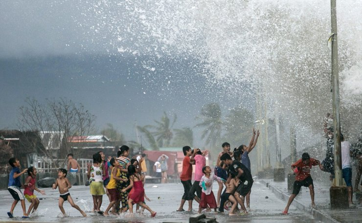 A handout photo made available by Greenpeace-Philippines shows children splashed by strong waves along a dike in the aftermath of Typhoon Kammuri in Legazpi city, Albay Province, Philippines, 03 December 2019. EPA
