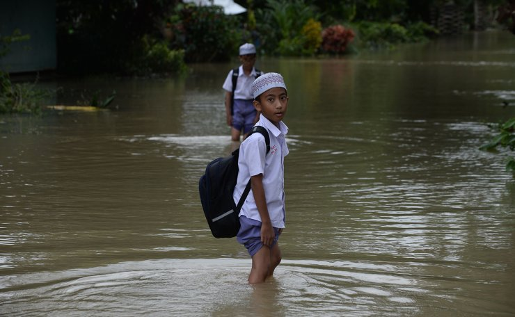 School children walk in floodwaters following heavy rains in southern Thailand's province of Narathiwat on December 3, 2019. AFP